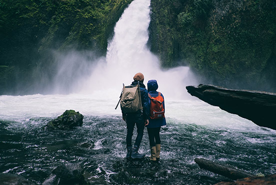 Two hikers looking at a waterfall, in a photo about to be shared on Facebook with Do Camera.